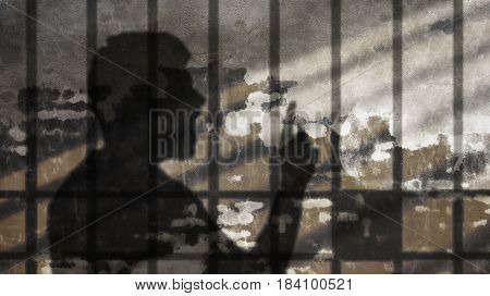 Man Shadow Talking behind Jail Bars. Freedom of Speech Metaphor on Concrete Wall.