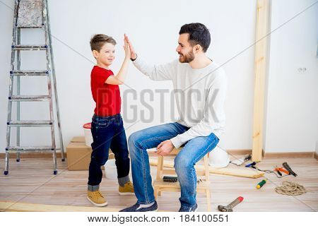 Father teaching his son to use saw