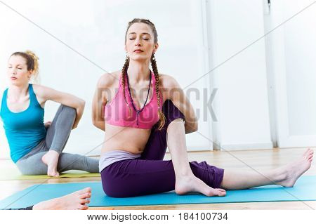 Portrait of two beautiful young women practicing yoga at home. Marichyasana pose.