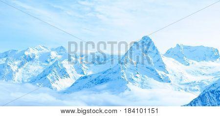 Beautiful Winter Snow Covered Peaks Of Caucasus Mountain, Dombaj Over Clouds, Russia, Panorama