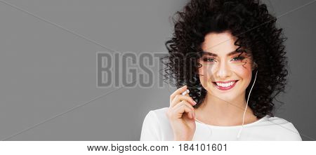 Portrait of happy woman putting on headphones on gray background with copy space