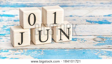 June 1st. Wooden cubes with date of 1 June on old blue wooden background.