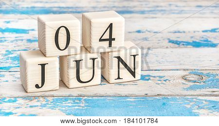 June 4th. Wooden cubes with date of 4 June on old blue wooden background.