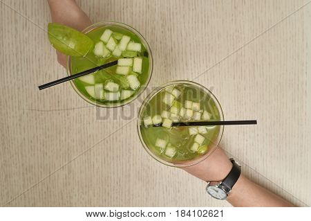 Two glasses of apple martini. Woman hands holding cocktails. Top view, overhead view or flat lay.