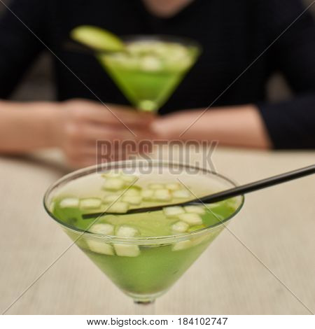 Two glasses of apple martini and apple slices on table in cafe. Young woman blurred at background