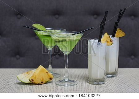 Apple martini and pina colada cocktails and apple and pineapple slices on table in cafe