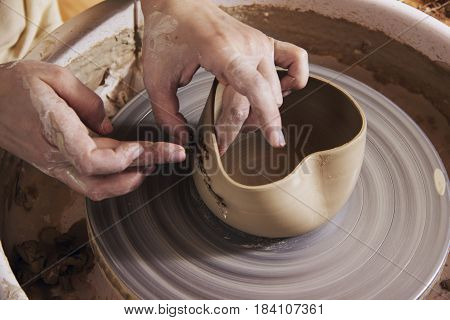 Close-up of the hands of a craftsman ceramist working with her potter wheel