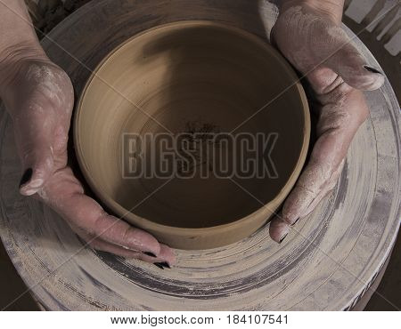 Close-up of the hands of a craftsman ceramist working with his potter wheel
