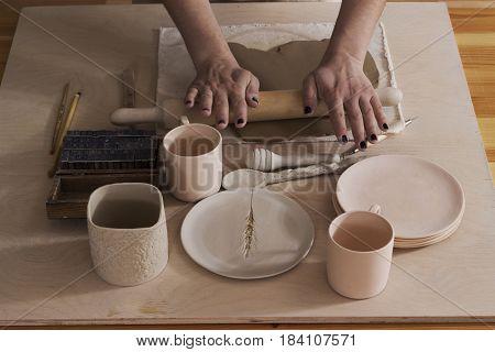 Closeup of woman ceramist hands working on sculpture on wooden table in workshop.Ceramist workshop