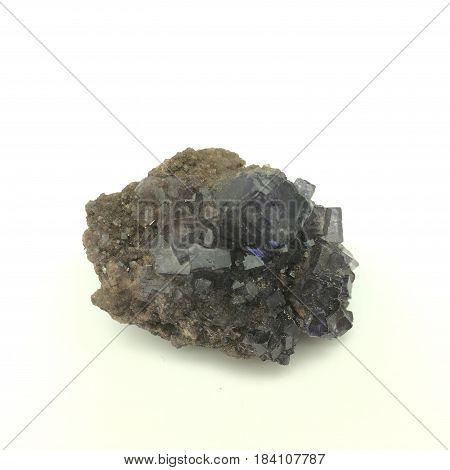 a small purple fluorite crystal formation on a plain rock matrix