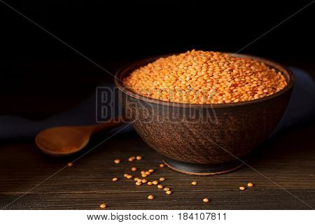 Red Lentils In Clay Bowl With Spoon And Fabric On Rustic Wooden Table.