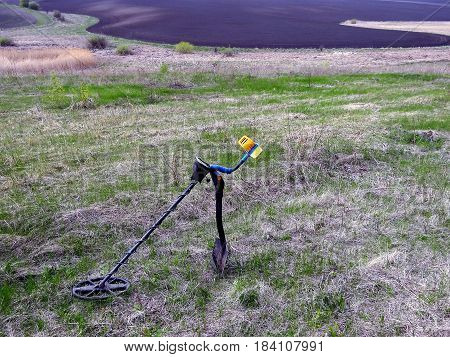 The metal detector on the shovel green meadow