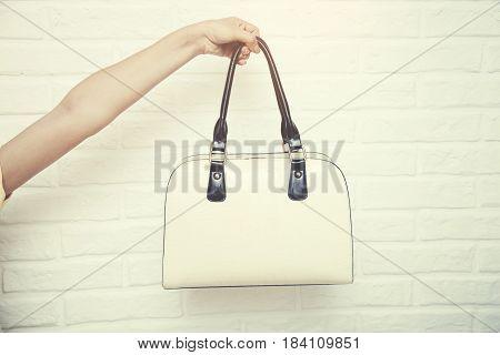 female hand holding bag on white brick background