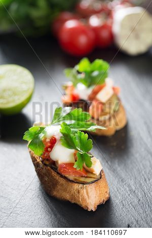 Tasty savory tomato Italian bruschetta, on slices of toasted baguette garnished with parsley, garlic. close up on a wooden black board