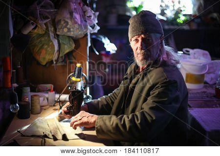 Old Man Sewing At Home