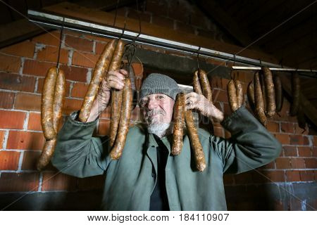A front view of an old man posing and goofing with dry sausages hanging in the attick.