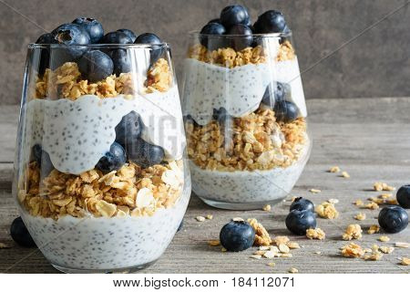 blueberry yogurt parfait with granola, oats and chia seeds in glasses on rustic wooden table. healthy breakfast. close up