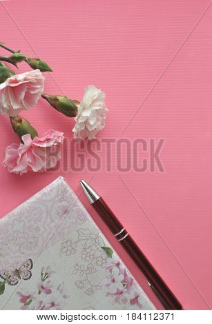 Pink carnations and floral notebook with red pen on a bright pink background, styled feminine image with copy space
