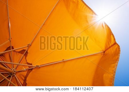 Yellow umbrella for sun protection in a summer resort