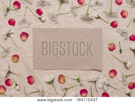 Decorative frame of cherry blossom flowers and red rose petals on old kraft paper. Template for design. Flat layout, top view