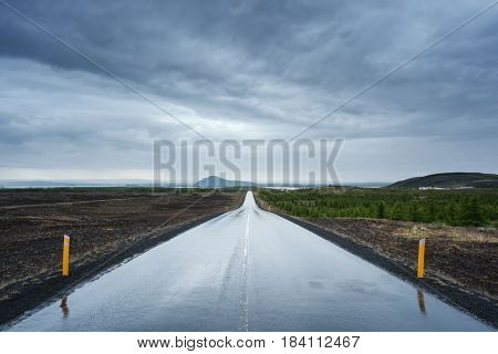 Wet road after the rain. Stormy sky with dark clouds. Near Lake Myvatn, Iceland