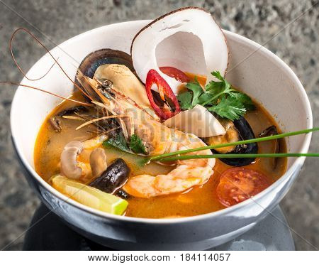 Tom Yum Goong thai soup over concrete background