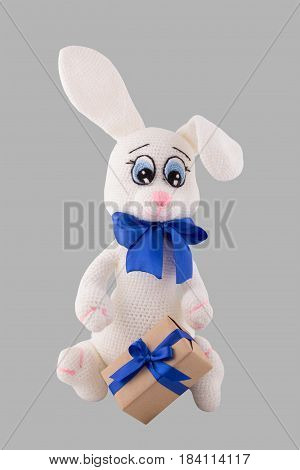 Knitted white bunny with a gift box. Easter rabbit is handmade. Soft knitted toys. Isolated on gray