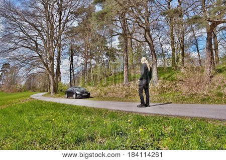 Zahradky Machuv kraj Czech republic - April 14 2017: Photographer Jiri Igaz is looking to his parked car Opel Astra at a road leading into colony Karba in Machuv kraj region in spring czech landscape