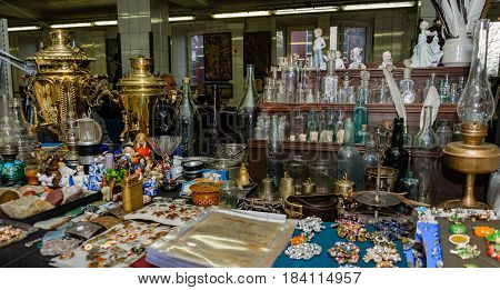 Moscow, Russia - March 19, 2017: Table at the antique market with old bottles and flacons for alcohol, medicines and perfumes of various sizes and colors, and with porcelain figurines and bronze samovars