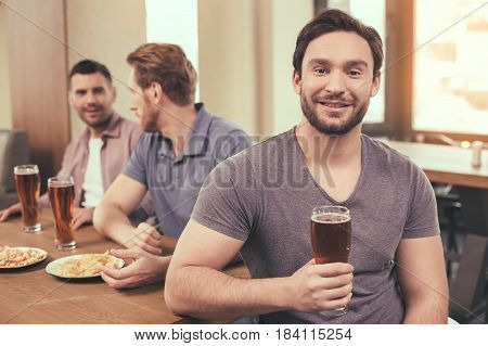 Pizza time. Friends spending time together in restaurant. Guys drinking beer and eating pizza. One man smiling and looking at camera