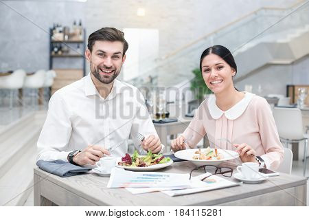 Business meeting. Business people discussing strategy. Businessman and woman in luxury restaurant. They having meal and coffee. Woman and man looking at camera