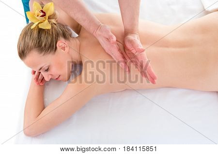 Top view of a professional masseuse doing back massage to woman client
