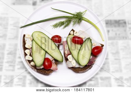 Plate with sliced lard bread tomates cucumber and garlic. Russian traditional cuisine. Best appetizer for vodka. 2 butties on a newspaper.