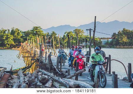 Vietnam Nha Trang - April 10 2017: Old wooden bridge and Vietnamese motorcyclists Motobikes
