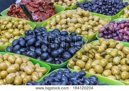 In large bowls laid out olives of different colors olives cucumbers and meat. Little pickles is inserted into green olives.