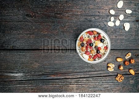 Bowl of granola, corn flakes and nuts on the dark wooden surface. Flat lay.
