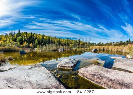 Cirrus clouds are reflected in the Winnipeg River. Indian summer in Manitoba, Canada. Old Pinawa Dam Park. The concept of ecological and recreational tourism