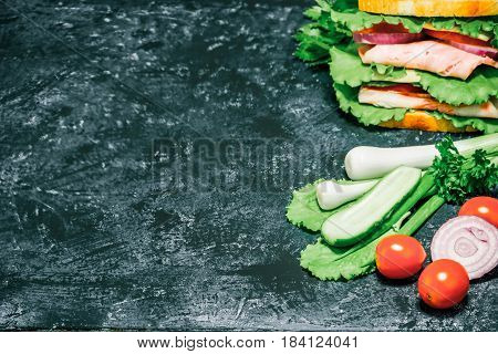 Double sandwich of bread, ham, cheese, tomato, cucumber, onion and lettuce on spotty grey background. Selective focus