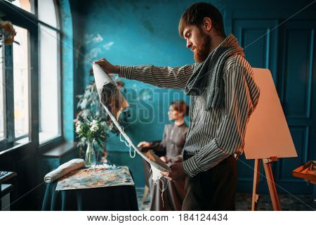 Painter looking at canvas painting against poseur