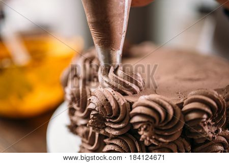 Decoration of chocolate cake with culinary syringe