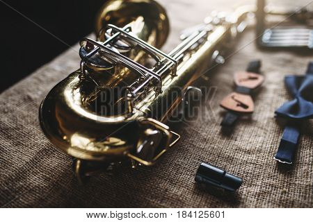 Saxophone, mouthpieces and bowtie, sack background