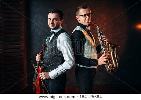 Saxophonist with sax and violinst with violin duet