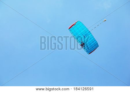 Tandem jumping with a blue parachute. Two skyscrapers on a parachute in the background blue sky.