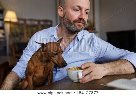 The Man Is Resting With His Dog. He Reads The Book, And The Dog Discreetly Tastes Coffee From His Cu