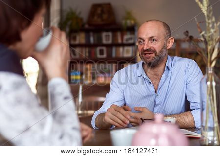 A Handsome Man In A Shirt Enthusiastically Tells His Girlfriend Something And Drinks Tea. Meeting At