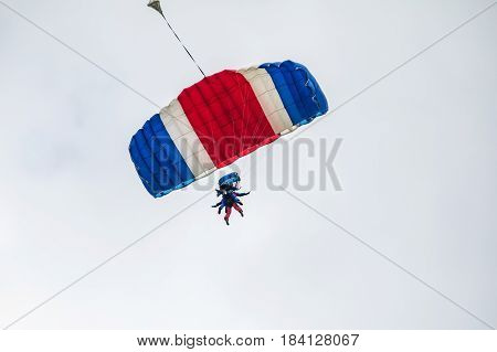 Tandem jumping with a blue parachute. Two skyscrapers on a parachute in the background blue sky. Parachutists fly to the sky. Two tandems with parachutists in the air.