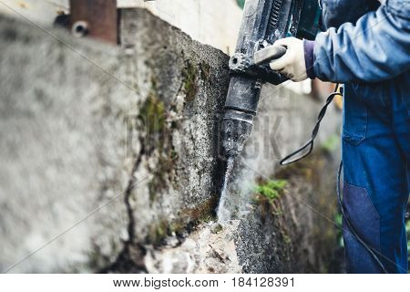 Worker Using Industrial Construction Tool, Industrial Jackhammer With Demolition Debris And Cement..