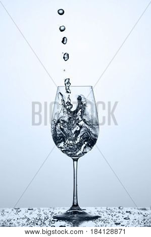 Pouring and splashing cleaner drinking water on a wineglass while standing on the glass with drapes against light background. Pure, transparent, useful water. Care fot the environment. Helathy lifestyle.