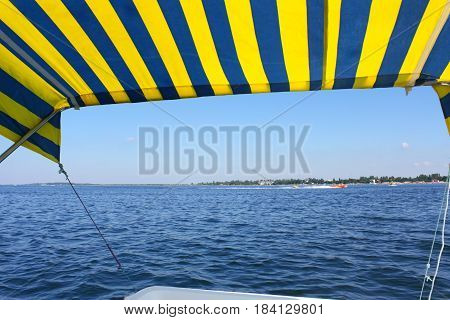 Blue and yellow catamaran tent above water surface near distant seashore in cloudless summer day