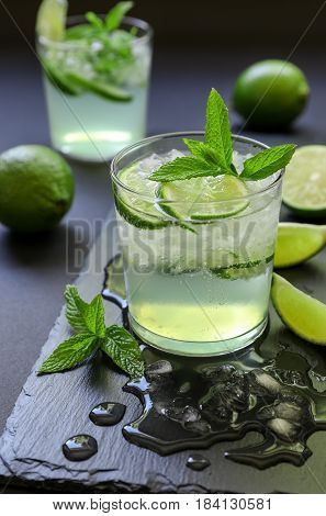 Cold cocktail with lemon liqueur, lime, tonic, ice in two glasses or mojito cocktail on dark background, copy space. Vertical. Close-up.